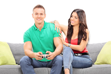 Girl watching her boyfriend play video game seated on a sofa