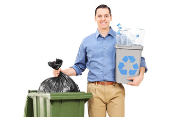 Man holding a recycle bin by a trash can