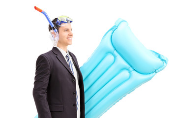 Man with suit and snorkel carrying swimming mattress
