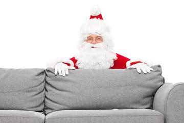 Santa Claus hiding behind a sofa
