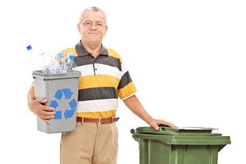 Senior holding recycle bin and standing by trash can