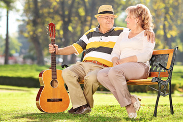 Mature man sitting with his wife in park and holding guitar