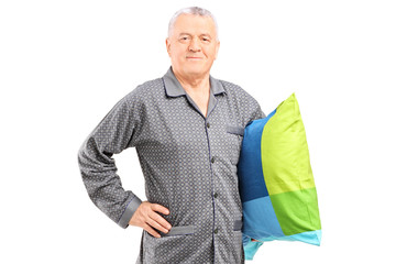 Senior in nightwear holding a pillow