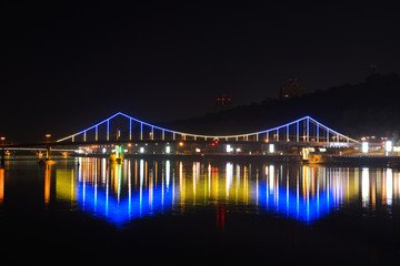 Glowing colored lights bridge across the Dnieper River in Kiev