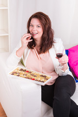 Plump woman at home eating chocolates and drinking wine