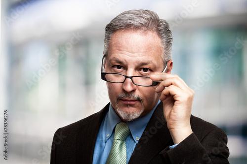 Mature businessman holding his eyeglasses - 76386276