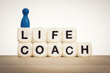 Life coach concept with toy dice and pawns