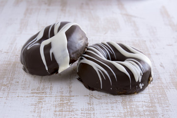 Two chocolate covered donuts in black and white