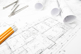 Construction planning drawings rolled on the worktable