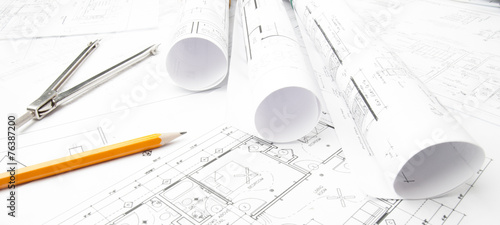 Construction blueprints rolled on the worktable - 76387200