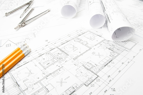 Construction planning drawings rolled on the worktable - 76387210