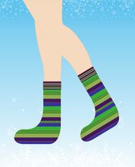 Girl in warm knitted woolen socks on winter background