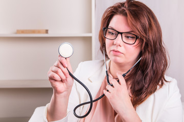 Young female doctor with a stethoscope examine
