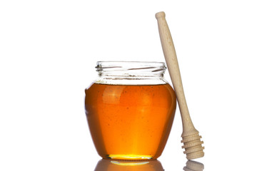 Glass jar of honey with wooden drizzler on a white background.