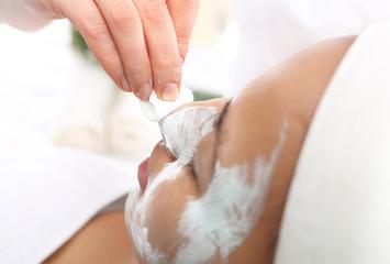 Zmywanie, oczyszczanie skóry twarzy, kobieta u kosmetyczki