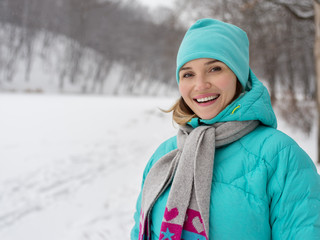 Portrait of young happy woman in blue jacket at the winter park.