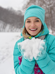 Portrait of young happy pretty woman with snow in palms