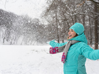 Happy woman in blue jacket at the winter park.