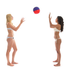 Young adult woman playing with beach ball