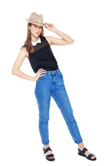 Young fashion girl in jeans and hat posing isolated