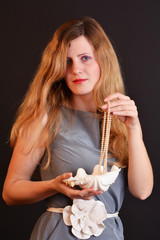 Blonde sensual woman holding a big seashell with pearls
