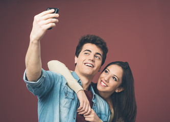 Young couple taking selfies