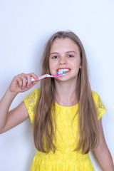 Young girl brushing her teeth. On gray background