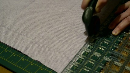 Hands cutting piece of fabric with fabric cutter.