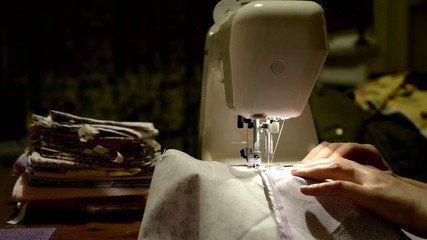 Hands stitching piece of fabric on automatic sewing machine