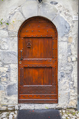 Red wooden door with large iron nails