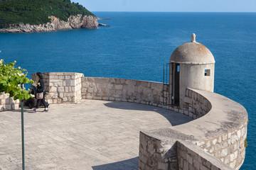 Tourist walks by gun turret on old city walls