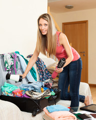 girl trying to find room for all the things in trunk