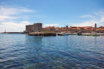 Small boats in city port with St. John fortress in background.