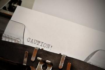 Caution text typed on old black typwriter