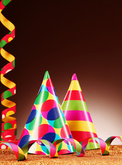 Colored Party Hats and Streamers on Gradient Brown