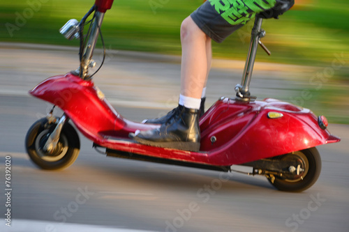 Young boy riding a vintage electric scooter - 76392020