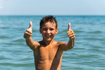 Young beautiful boy showing thumb up sign in the sea