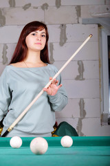 photo of a beautiful woman holding a pool cue