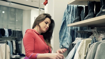 Young woman checking clothes at shopping store
