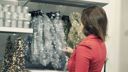Young woman checking christmas decoration at shopping store