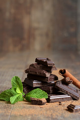 Stack of chocolate slices with mint leaf and cinnamon.