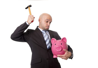 businessman with hammer  to break huge pink piggy bank