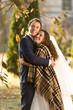 smiling bride and groom hugging under plaid at autumn park