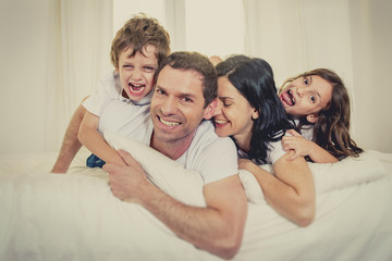 happy Brazilian family together on bed having fun smiling