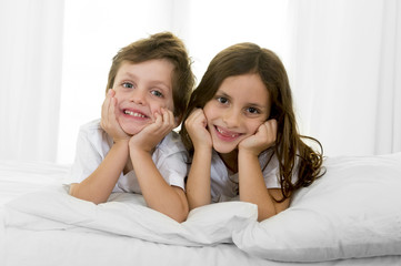 happy sweet little brother and sister on bed couch together