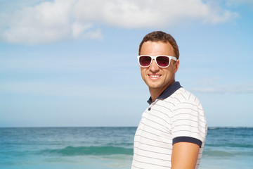 Man standing with white sunglasses on summer sea coast