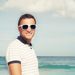 Young man standing with sunglasses on sea coast