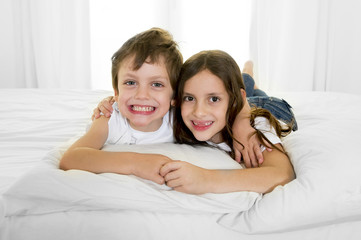 happy sweet little brother loving sister on bed couch together