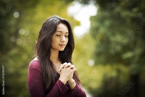 Woman praying outdoors - 76395097