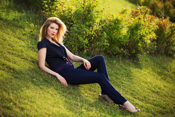 Young fashion woman sitting on the grass outdoor